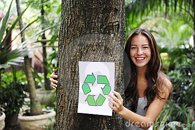 Recycling: woman in forest with recycle sign