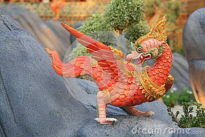 Red animal sculpture like chicken on the rock