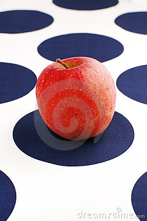 Red apple on blue and white table cloth
