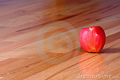 Red Apple on Hardwood Floor