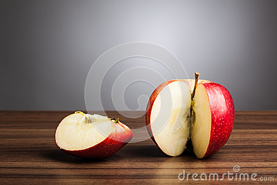 Red apple  on table with sliced piece, gray background