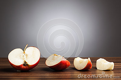Red apple on table with sliced pieces, gray background
