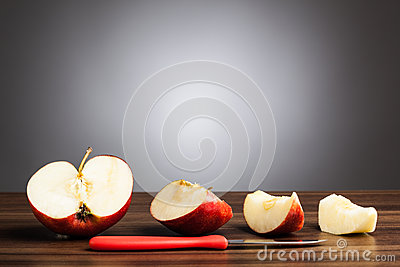 Red apple on table with sliced pieces and knife, gray background