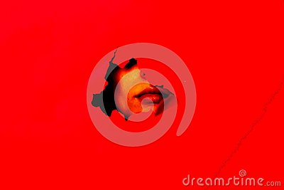On the red background, the face can be seen in the hole Stock Photo