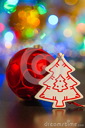 Red ball and white wooden Christmas tree on a background of ligh