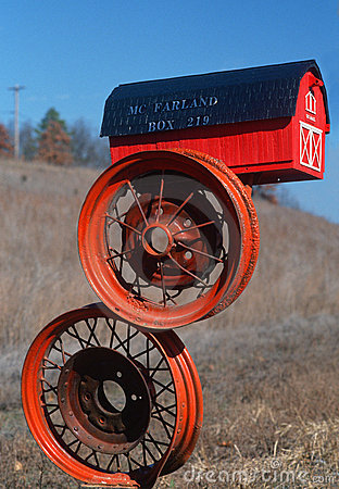 Red barn mailbox on tire rims Editorial Photography