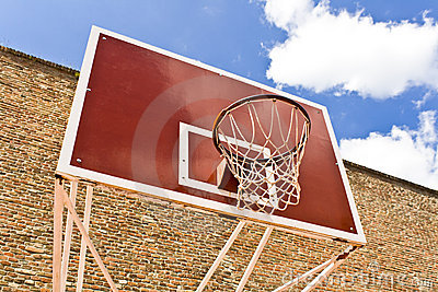 Red basketball board over brick wall and blue sky