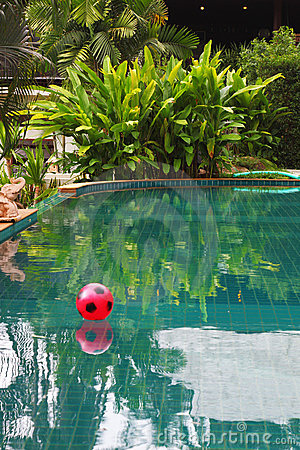 Red beach ball floating in pool