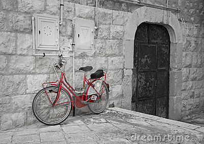 Red bicycle leaning against wall.