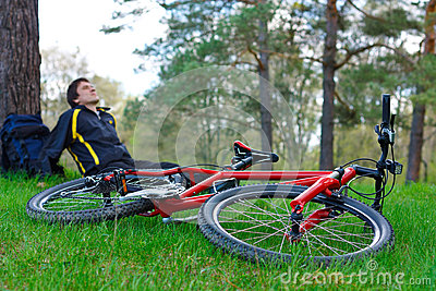 Red Bike Lying on Green Grass. Cyclist Relaxes