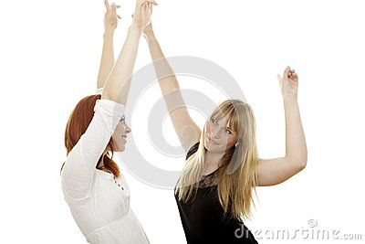 Red and blond haired girls dance with arms in air