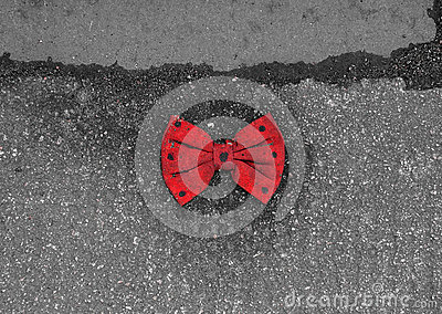 Red bow tie with black dots lying on the pavement