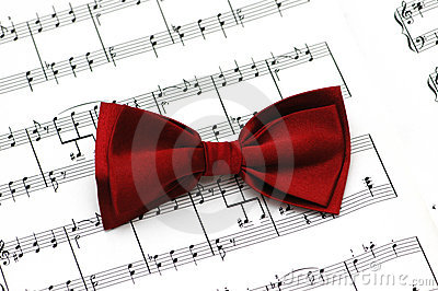 Red bow tie on musical notes paper