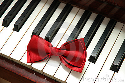 Red bow tie on white piano key
