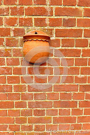 Red brick wall with flower pot