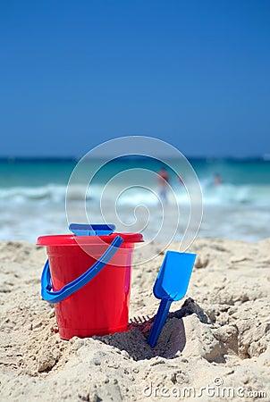 Red bucket and blue spade on sunny sandy beach