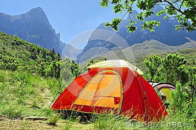 Red camping tent in misty mountains - springtime colors