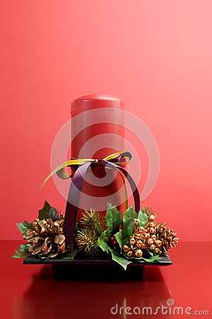 Red candle with holly and pine cone Christmas table centrepiece still life