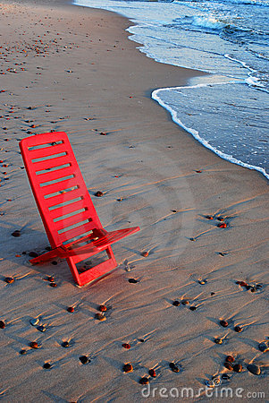 Red chair on the shore