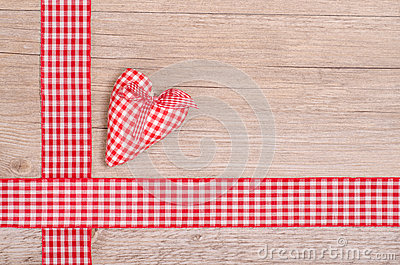 Red checkered heart and ribbon on wood