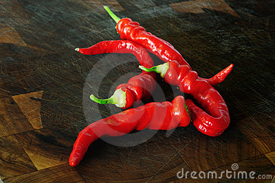 Red chile peppers on a wooden chopping board