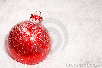 Red Christmas bauble on a bed of snow