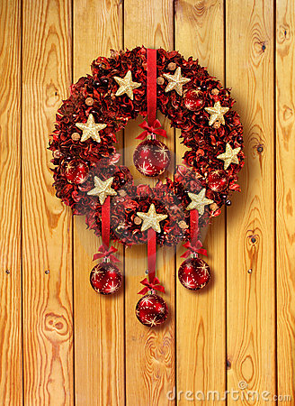 Red Christmas garland in wooden door