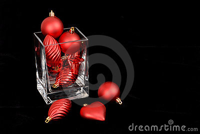Red Christmas ornaments in and around a glass vase