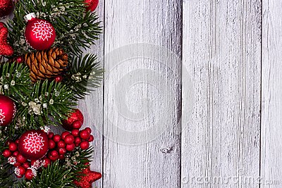 Red Christmas ornaments and branches side border on white wood Stock Photo