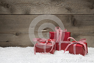 Red Christmas presents with checkered bows on grey wooden backgr