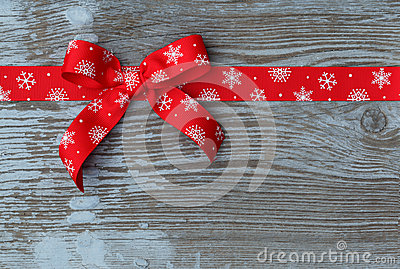 Red christmas ribbon bow on wooden board