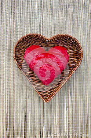 Red cloth heart symbol in wicker basket