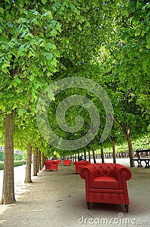 Red club sofas in  a garden