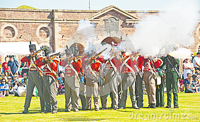 Red coat soldiers firing rifles at Fort George Editorial Stock Image