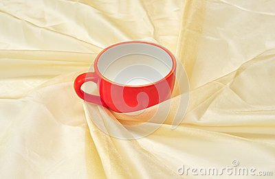 Red cup at the golden fabric drapery