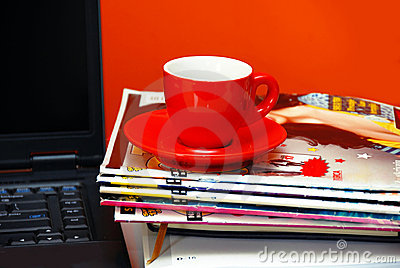 Red cup on magazines and notebook over red