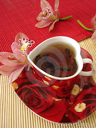 Free Red Cup Of Tea In The Form Of Heart With Pink Orchids Over Straw Royalty Free Stock Image - 2052506