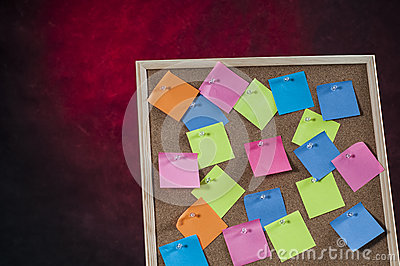 Red dangerous background with cork board full with colored post notes