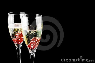 Red dice in a champagne flute