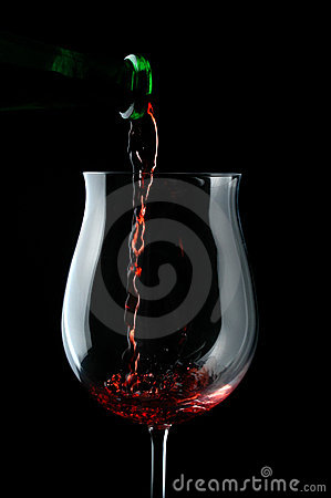 Red drops wine being poured into a wine glass