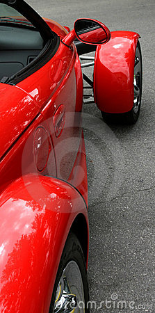 Red exotic sports car with view in side mirror
