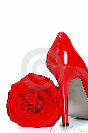 Red female shoes with high heels and a flower.
