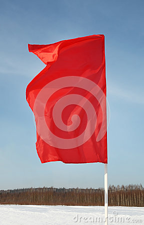 Red flag flutters in wind at background of sky