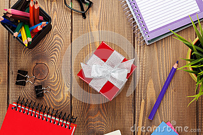 Red gift box and office supplies over office table