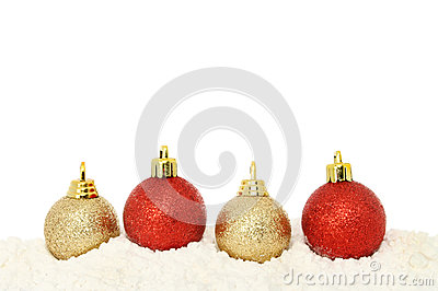 Red and gold baubles on snow