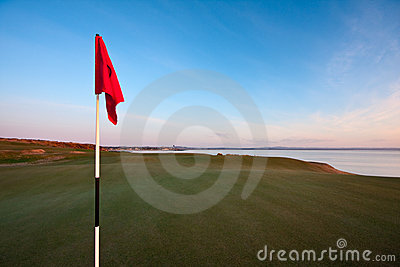 Red golf flag on a green at dawn