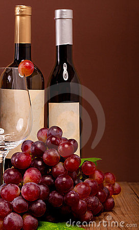 Red grapes with wine bottles