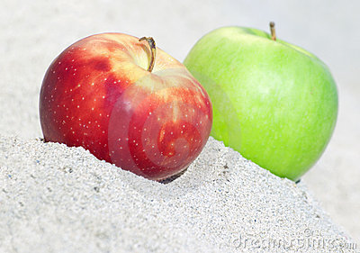 Red and green  apples on sand