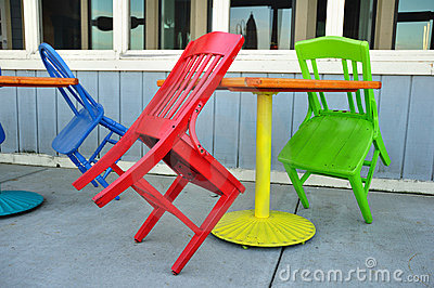 Red, Green, and Blue Chairs Leaning on Tables