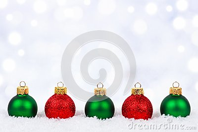 Red and green Christmas ornaments in snow with twinkling background Stock Photo